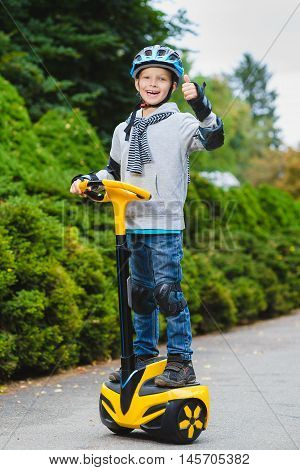 Happy boy standing on hoverboard or gyroscooter outdoor.