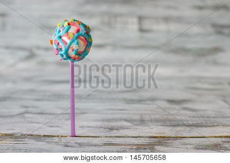 Ball-shaped dessert with glaze. Pink and blue icing. Special recipe of cake pop. Nice surprise for your kid.