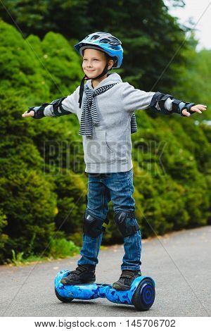 Happy boy riding on hoverboard or gyroscooter outdoor.