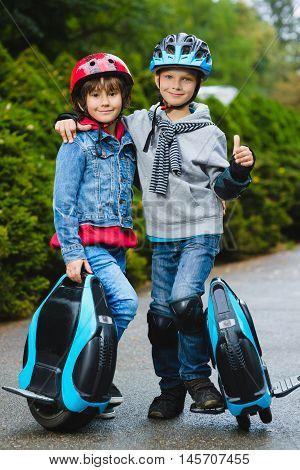 Happy kids standing near mono-wheel hoverboard or gyroscooter outdoor.