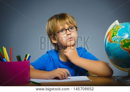 school concept. doubt, expression - boy thinking over gray background.