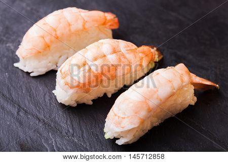 Close-up of Ebi sushi with shrimp on a black slate background