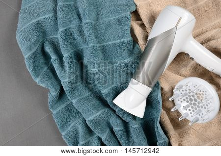 White Hairdryer On Beige And Greenish-blue Towels. Top View