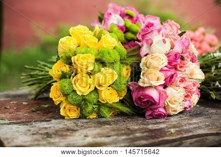 Two bouquets of pink and yellow roses on a wooden florist's table