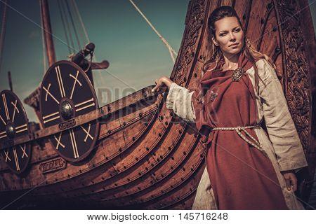 Beautiful viking woman standing near Drakkar on the seashore.
