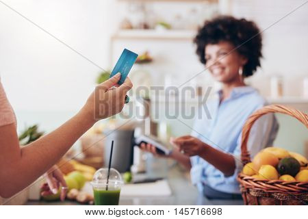 Customer Paying For Their Order With A Credit Card In Juice Bar