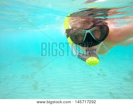 Portrait of a young woman swimming underwater in the clean blue sea of Protaras Cyprus. View of snorkeling tube mask bikini of free diver near the surface of the water.