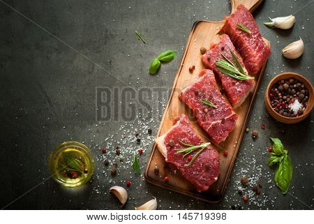Raw meat. Raw beef steak on a cutting board with rosemary and spices.
