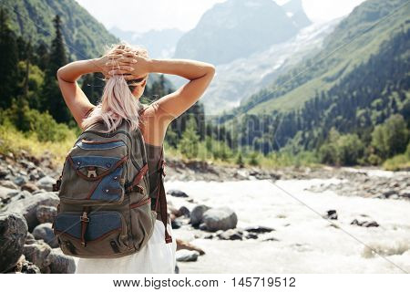Backpacker walking by the river. Traveler standing and looking at beautiful view.