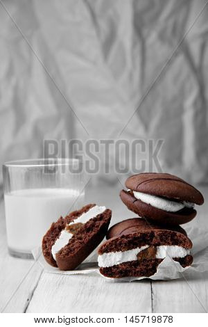 Broken Cookies And Stack Of Sponge Cookies With Cream On Paper. Closup.glass With Milk Defosused On