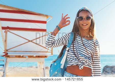 10 years old child wearing cool clothing posing with colorful skateboard on the beach, urban style, pre teen summer fashion.