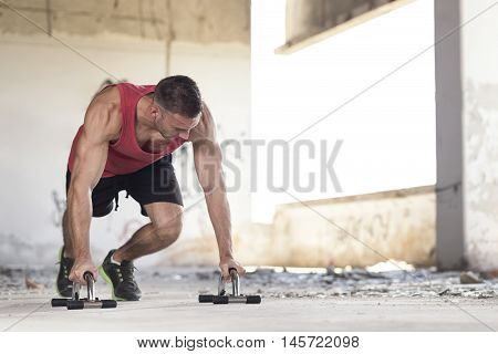 Muscular athletic built young man doing pushups in an abandoned ruin building