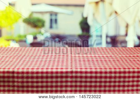 Table with red checked tablecloth over blur restaurant background