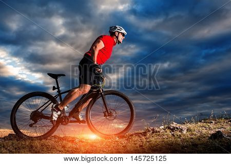 mountain bicycle rider on the hill with sunrise and cloudy sky background