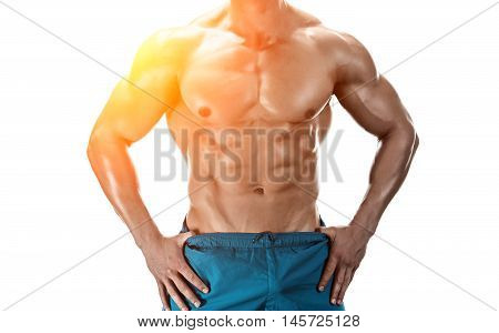 Strong Athletic Man showing muscular body and sixpack abs isolated white background. Close-up. with sun flare