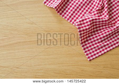 Checked tablecloth on wooden table. View from above with copy space