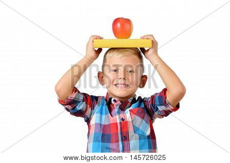 Portrait of happy schoolboy with book and apple on his head isolated on white background.Education isolated. School preschool