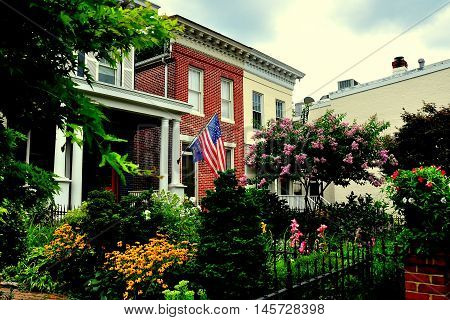Baltimore Maryland - July 24 2013: 19th century homes with colourful gardens on Montgomery Street in the Federal Hill National historic district *