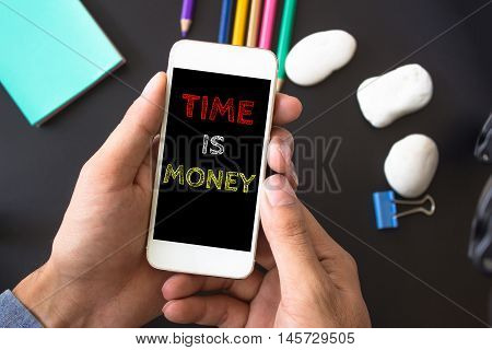Time is money, text message on screen at hands take smartphone, black table with office supplies backdrop background . business concept.