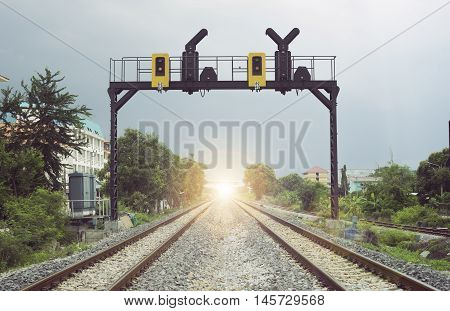 two parallel railway pass in a city with a railway traffic light,light of life concept,fighting for light mean
