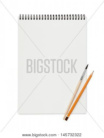 Top view of blank sketchbook with pencil and brush isolated on white