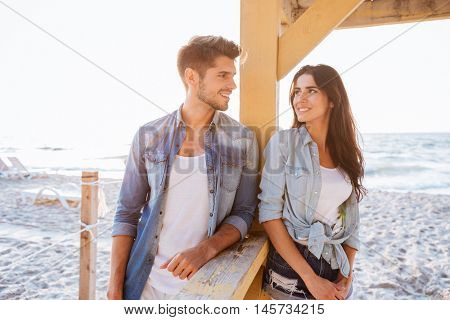 Young cheerful beautiful couple flirting at the beach
