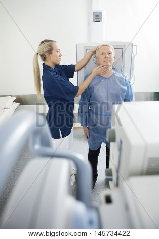 Radiologist Adjusting Head Of Patient Before Taking Xray