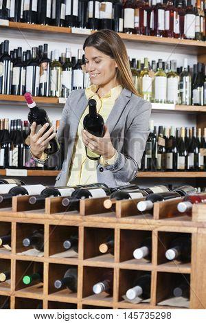 Female Customer Looking At Wine Bottles In Winery