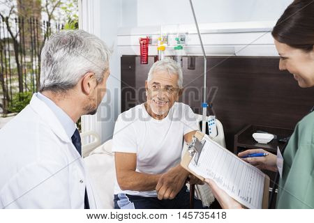 Patient Looking At Doctor While Nurse Holding Reports