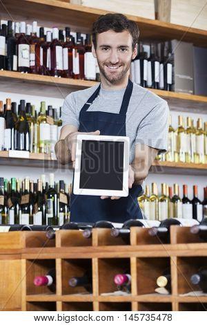 Salesman Showing Blank Tablet Computer In Wine Shop