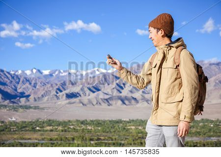 Asian Young Traveler Looking At Compass In Himalaya Mountain View Background