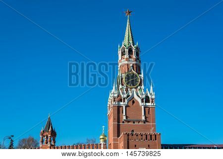 Spasskaya tower of Moscow Kremlin with chiming clock against the blue sky. poster