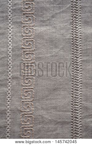 Background fragment of the hand embroidery on linen. Openwork pattern of longitudinal strips