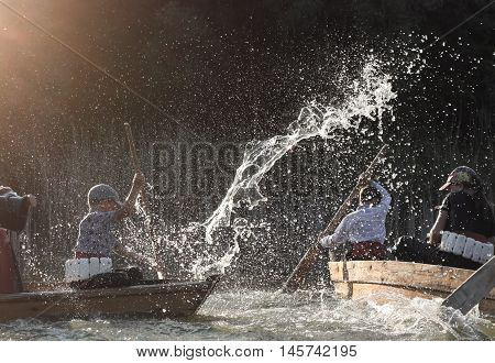 Children under the spray of water sitting in a boat and rowing oars