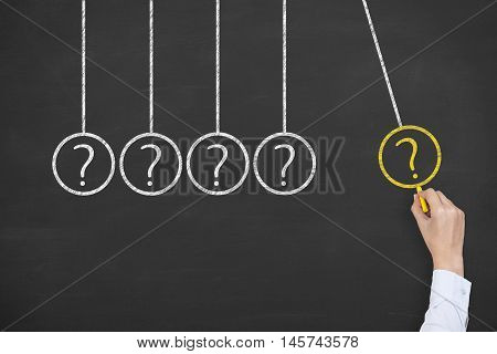 Newton Cradle Question on Chalkboard Background Business Concept