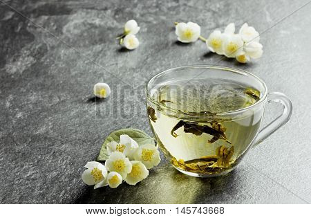 Cup of flavored japanese green tea with jasmine flowers on a black stone background. Focus is on the front of the cup.