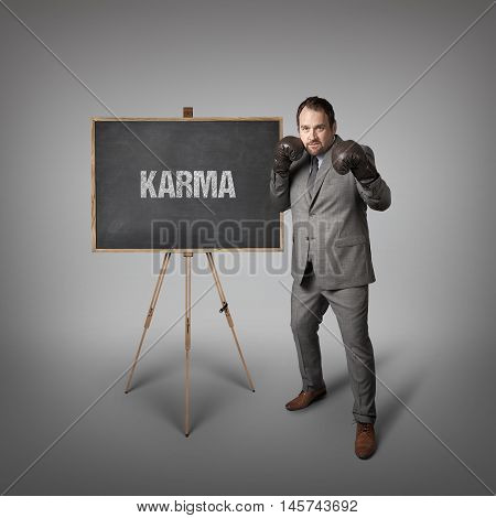 Karma text on  blackboard with businessman wearing boxing gloves