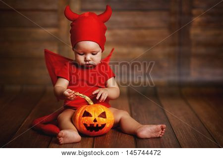 funny baby in devil halloween costume with pumpkin on a dark wooden background
