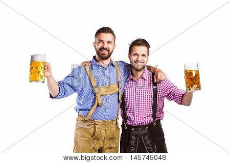 Two handsome hipster young men in traditional bavarian clothes holding mugs of beer, clinking. Oktoberfest. Studio shot on white background, isolated.