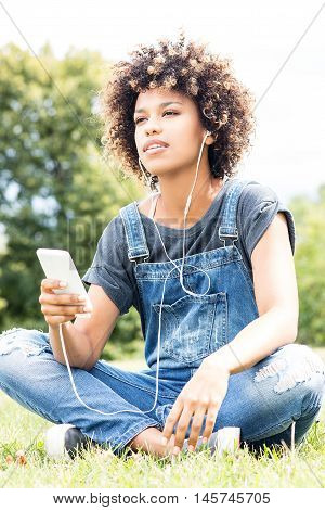 Young Girl Listening To Music In Park, Relaxing.