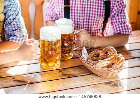 Two unrecognizable men in traditional bavarian clothes sitting at the table, holding mugs of beer, clinking. Pretzels in basket. Oktoberfest.