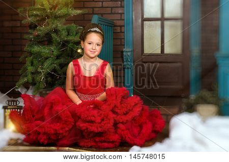 Little winter Princess in a precious crown in red dress welcomes New year and Christmas in enchanting Christmas interior with decorated pine tree and artificial snow