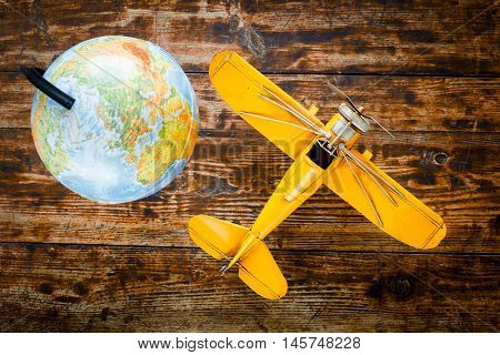 concept - time to travel plane, globe on wooden table