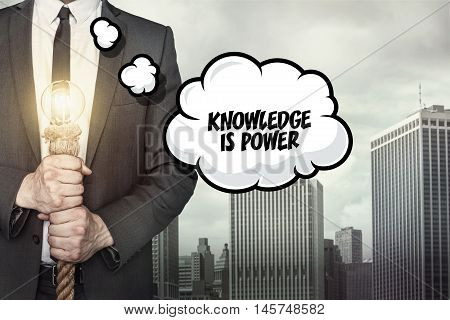 Knowledge is power text on speech bubble with businessman holding lamp
