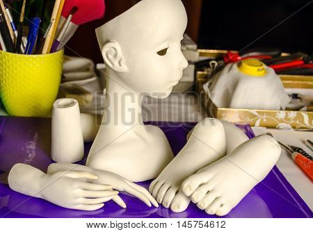 The process of making dolls. Different parts of the doll on the working surface.