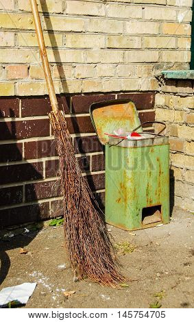 Dirty dustbin and broom near a wall outdoors.