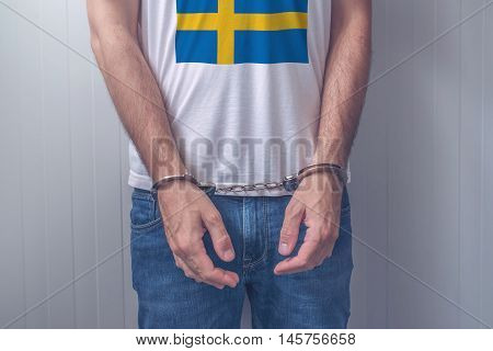 Arrested man with cuffed hands wearing shirt with Swedish flag. Unrecognizable male person in jeans with handcuffs held in police station for being suspected of a crime.
