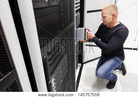 It engineer or consultant working with installation of a blade server in data rack. Shot in enterprise datacenter.