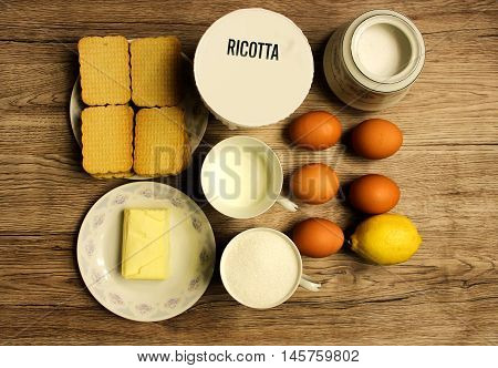 A set of products for the preparation of cheesecake on a wooden background.