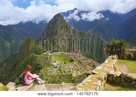 Woman enjoying the view of Machu Picchu citadel in Peru. In 2007 Machu Picchu was voted one of the New Seven Wonders of the World.